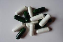 Gruppo di capsule bianche di citrato di magnesio e di capsule verdi dei multivatamins fotografie stock