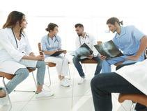 Gruppo di chirurghi e di professionisti medici che discutono sulla radiografia paziente Immagini Stock Libere da Diritti