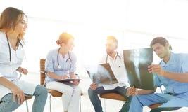 Gruppo di chirurghi e di professionisti medici che discutono sulla radiografia paziente Immagine Stock