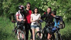 Gruppo di ciclisti che controllano la mappa in compressa che discute l'itinerario archivi video