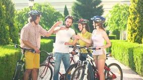Gruppo di ciclisti che giocano le roccia-carta-forbici archivi video