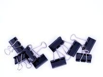 Gruppo di clip del bulldong del nero del metallo sui precedenti bianchi Fotografia Stock Libera da Diritti