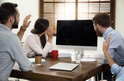 Gruppo di colleghi che utilizzano video chiacchierata sul computer nell'ufficio immagini stock libere da diritti