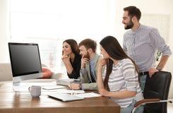 Gruppo di colleghi che utilizzano video chiacchierata sul computer nell'ufficio immagine stock libera da diritti