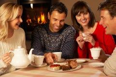 Gruppo di coppie che gode insieme del tè e della torta immagini stock libere da diritti