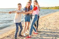 Gruppo di corda di trazione dei bambini durante il gioco di conflitto sulla spiaggia Campeggio estivo fotografie stock libere da diritti