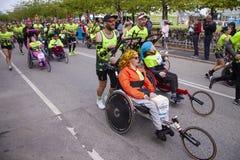 Gruppo di corridori maratona che spingono eseguendo le sedie a rotelle con le persone disabili che le aiutano per compiere il fun immagini stock