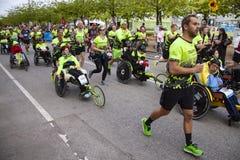 Gruppo di corridori maratona che spingono eseguendo le sedie a rotelle con le persone disabili che le aiutano per compiere il fun fotografia stock