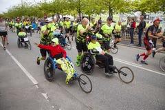 Gruppo di corridori maratona che spingono eseguendo le sedie a rotelle con le persone disabili che le aiutano per compiere il fun fotografia stock libera da diritti