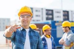 Gruppo di costruttori sorridenti in elmetti protettivi all'aperto Fotografia Stock