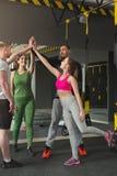 Gruppo di dare sportivo della gente alto--cinque alla palestra Fotografia Stock