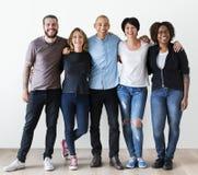 Gruppo di diversi amici che sorridono insieme e che abbracciano Immagine Stock