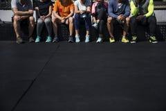 Gruppo di diversi atleti che si siedono insieme immagini stock