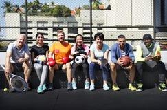 Gruppo di diversi atleti che si siedono insieme fotografia stock libera da diritti