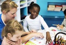 Gruppo di diversi bambini che colorano libro di esercizi nella classe Fotografia Stock