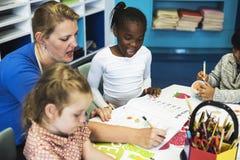 Gruppo di diversi bambini che colorano libro di esercizi nella classe Fotografia Stock Libera da Diritti