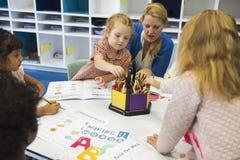 Gruppo di diversi bambini che colorano libro di esercizi nella classe Fotografie Stock Libere da Diritti