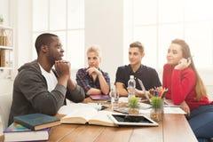 Gruppo di diversi studenti che studiano alla tavola di legno Immagine Stock