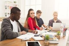 Gruppo di diversi studenti che studiano alla tavola di legno Fotografia Stock