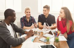 Gruppo di diversi studenti che studiano alla tavola di legno Immagini Stock