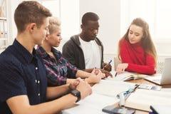 Gruppo di diversi studenti che studiano alla tavola di legno Immagini Stock Libere da Diritti