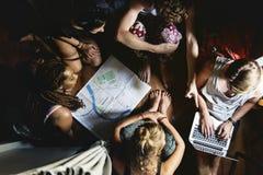 Gruppo di diversi turisti che si siedono sulla pianificazione di pavimento di legno che verifica la mappa Fotografia Stock Libera da Diritti
