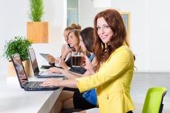 Gruppo di donna di affari graziosa che collabora con il nuovo progetto startup facendo uso del computer portatile in sottotetto m Fotografie Stock