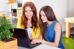 Gruppo di donna di affari graziosa che collabora con il nuovo progetto startup facendo uso del computer portatile in sottotetto m Immagini Stock Libere da Diritti