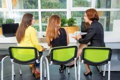 Gruppo di donna di affari graziosa che collabora con il nuovo progetto startup facendo uso del computer portatile in sottotetto m Fotografie Stock Libere da Diritti