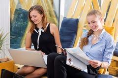 Gruppo di donna di affari graziosa che collabora con il nuovo progetto startup facendo uso del computer portatile in sottotetto m Immagine Stock