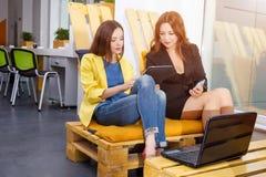 Gruppo di donna di affari graziosa che collabora con il nuovo progetto startup facendo uso del computer portatile in sottotetto m Fotografia Stock