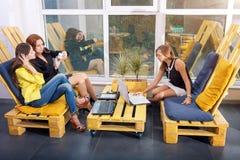 Gruppo di donna di affari graziosa che collabora con il nuovo progetto startup facendo uso del computer portatile in sottotetto m Fotografia Stock Libera da Diritti