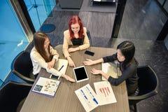 Gruppo di donne di affari che si incontrano in una sala riunioni con l'SCR in bianco immagini stock libere da diritti
