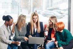 Gruppo di donne di affari multirazziali nell'abbigliamento casual che esamina insieme il computer portatile fotografia stock