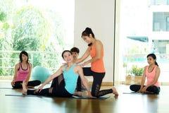 Gruppo di donne asiatiche e di yoga di pratica dell'uomo, allungamento di forma fisica Immagini Stock Libere da Diritti