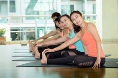 Gruppo di donne asiatiche e di yoga di pratica dell'uomo, allungamento di forma fisica Fotografia Stock