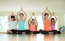 Gruppo di donne asiatiche e di yoga di pratica dell'uomo, allungamento di forma fisica Fotografie Stock Libere da Diritti