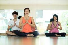 Gruppo di donne asiatiche e di yoga di pratica dell'uomo, allungamento di forma fisica Immagini Stock