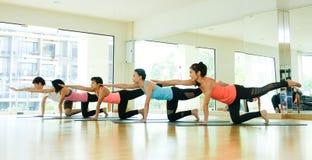 Gruppo di donne asiatiche e di yoga di pratica dell'uomo, allungamento di forma fisica Immagine Stock