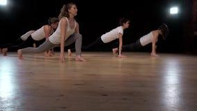 Gruppo di donne che allungano addestramento che si esercita nei pilates di pratica di yoga della palestra Studentesse di sport stock footage