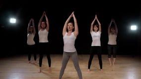 Gruppo di donne che allungano addestramento che si esercita nei pilates di pratica di yoga della palestra Studentesse di sport video d archivio