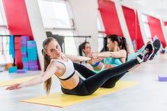Gruppo di donne che fanno partner che allunga gli esercizi durante la sessione di allenamento nel corridoio di forma fisica Fotografia Stock Libera da Diritti