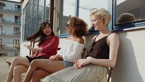 Gruppo di donne che si siedono all'aperto e di pettegolezzo archivi video