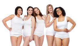 Gruppo di donne differenti felici in biancheria intima bianca Immagini Stock