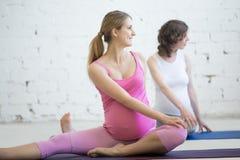 Gruppo di donne incinte che fanno yoga prenatale Torsione spinale a gennaio Immagine Stock