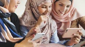 Gruppo di donne islamiche che parlano insieme e che guardano sul telefono Immagine Stock