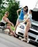Gruppo di donne vicino all'automobile rotta sulla strada Fotografia Stock