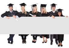Gruppo di dottorandi che presentano insegna vuota Fotografia Stock