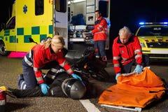 Gruppo di emergenza che assiste il driver danneggiato della motocicletta Fotografie Stock