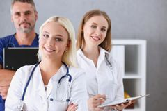 Gruppo di erba medica che posa fiero nella fila e che guarda in camera Fotografia Stock